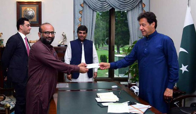 Faisal Edhi (left) who tested COVID-19 met Imran Khan on April 15 to present a cheque of Rs10 million to the Prime Minister for the coronavirus relief fund. (Image Credit: Social Media)