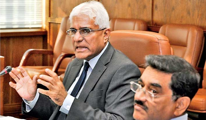 Central Bank Governor Dr.Indrajith Coomaraswamy gestures at the media briefing yesterday. Senior Deputy Governor Dr. Nandalal Weerasinghe looks on- Pic by Ruwan walpola