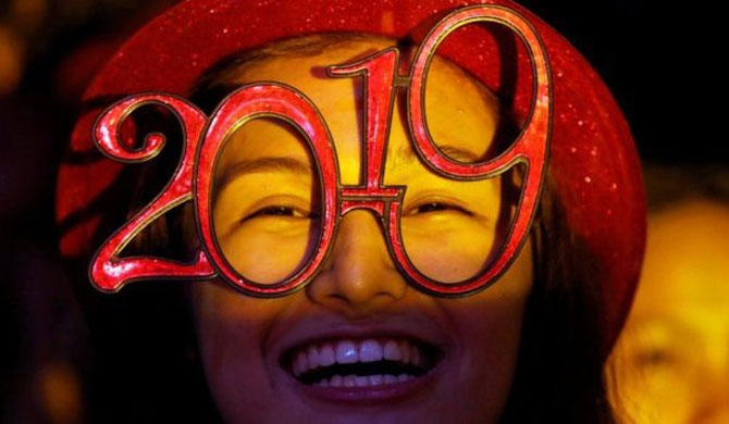 "A reveller wears glasses that spell out ""2019"" during a New Year's Eve party in Quezon City in the Philippines"