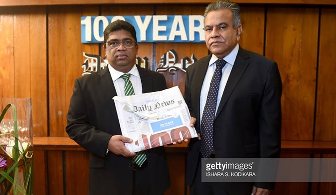 Chairman of the ANCL, Krishantha Cooray, poses for a picture with Chief Editor Lalith Allahakkoon (R) while holding the volume marking 100 years of their flagship Daily News edition in Colombo on January 3, 2018. (Courtesy : Ishara S. Kodikara/AFP/Getty Images)