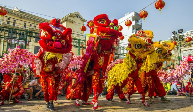 Chinese New Year celebrations feature dragon and lion dances. Credit: Saigoneer/Shutterstock